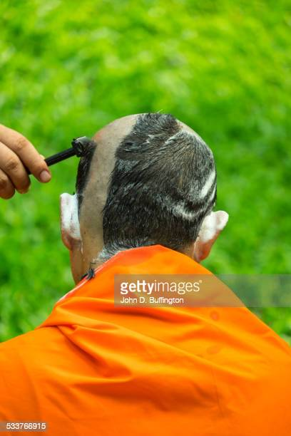 Buddhist monk shaving his head