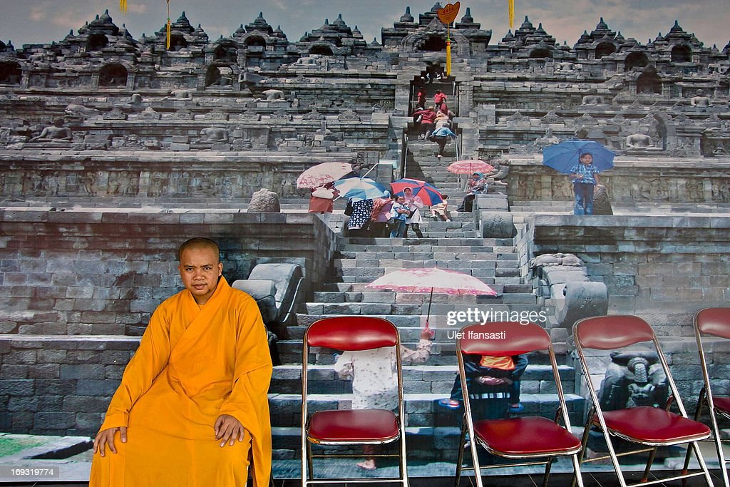 A Buddhist monk sits in front of borobudur wallpaper at the temple during Pindapata procession on May 23, 2013 in Magelang, Central Java, Indonesia. As many as 100 monks took to the streets of Magelang city in a procession known as Pindapata, ahead of Vesak day which celebrates the birth of the Lord Buddha.