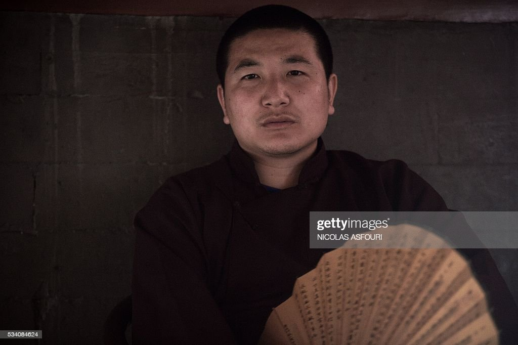 A Buddhist monk sits inside the Lama temple in Beijing on May 25, 2016. / AFP / NICOLAS