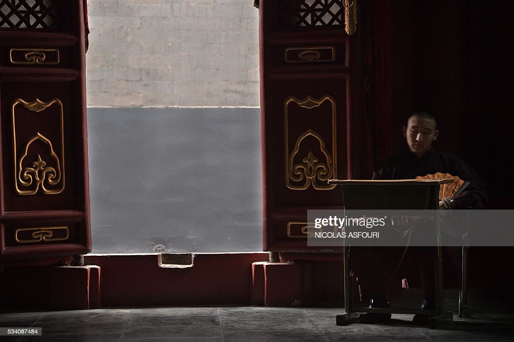 A Buddhist monk sits inside the Lama temple in in Beijing on May 25, 2016. / AFP / NICOLAS