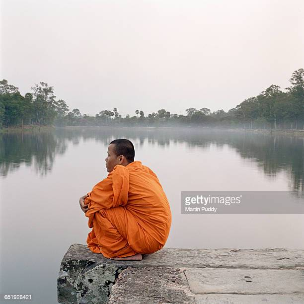 Buddhist monk sitting on steps at Angkor Wat