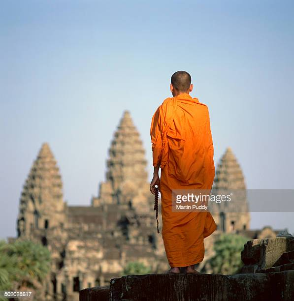 Buddhist monk standing in front of Angkor Wat