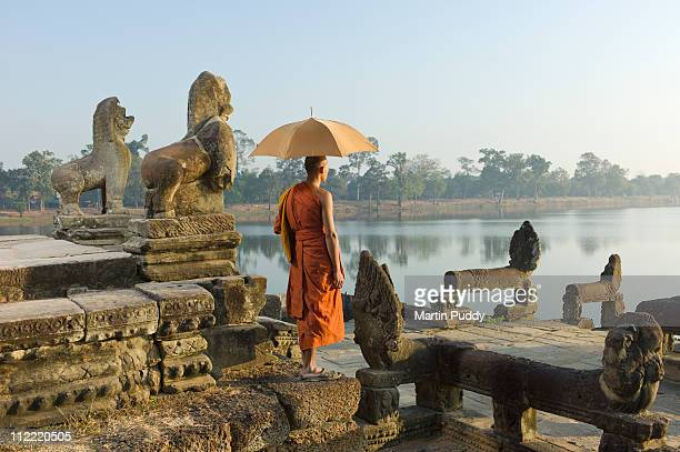 Buddhist monk standing next to stone carvings