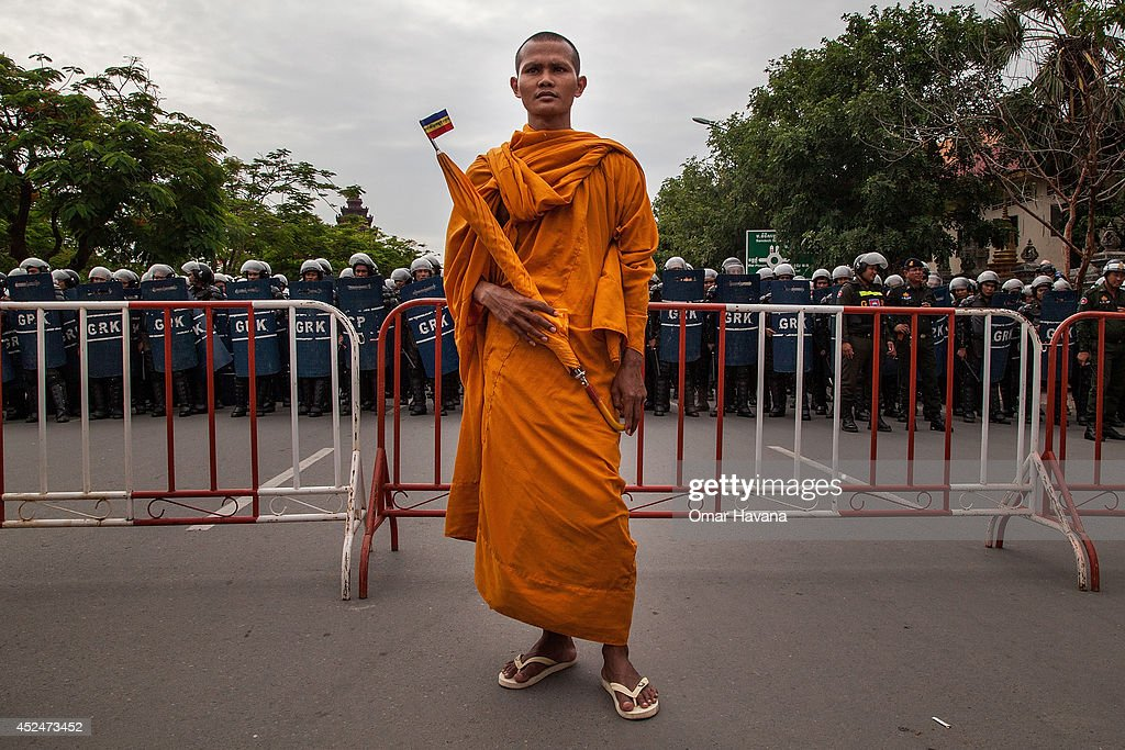 A Buddhist monk stands in front of a barricade heavily protected by police forces during a demonstration to deliver petitions to different embassies on July 21, 2014 in Phnom Penh, Cambodia. Thousands of protesters and monks march through the streets of Phnom Penh to deliver petitions to the French, British, American, Russian and Chinese embassies, before arriving at the Vietnamese Embassy. The protesters, organised by the Federation of Cambodian Intellectuals and Students (FCIS) and leaders of the Khmer Krom community, are demanding an apology from Vietnamese Embassy First Counsellor Tran Van Thong, who recently said that the former Kampuchea Krom provinces were held by Vietnam before their occupation by France. Ahead of the protest, Phnom Penh municipal authorities banned the protest, threatening the protesters who defied the ban could be jailed for up to 15 years.