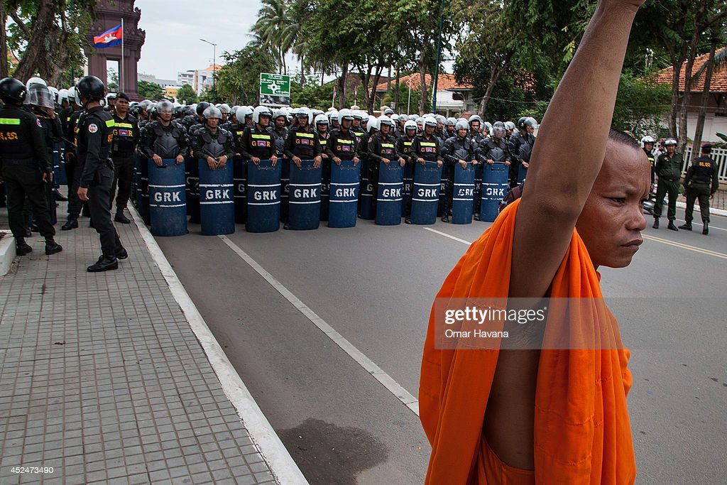 Buddhist monk stands in front of Cambodian police forces during a demonstration to deliver petitions to different embassies on July 21 2014 in Phnom...