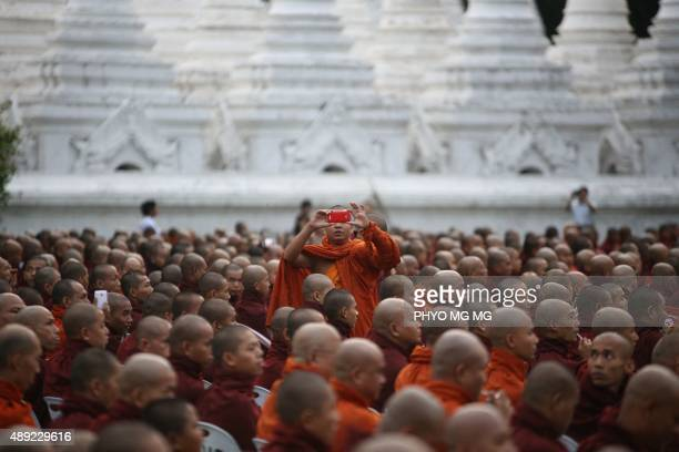 Buddhist monk takes a photo as he and other monks from Myanmar and Thailand are offered morning alms during the first ever MyanmarThailand friendship...