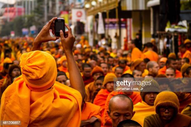 Buddhist monk using call phone to record moment at the gathering of 10000 monks in Chiang Mai Thailand