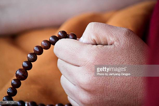 Buddhist monk using prayer beads
