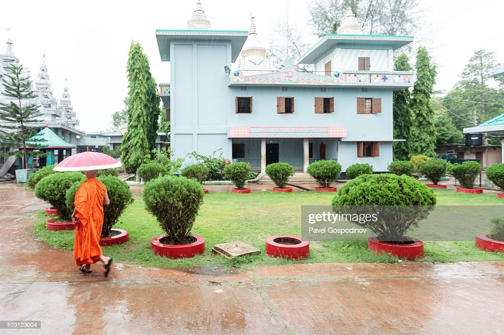 Buddhist monk walking in the rain in front of Rajbana Vihara, a renowned Buddhist Temple at Rangamati