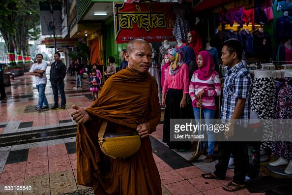 Buddhist monk walks around the streets to receive religious alms from Buddhist followers during Pindapata procession on May 21 2016 in Magelang...