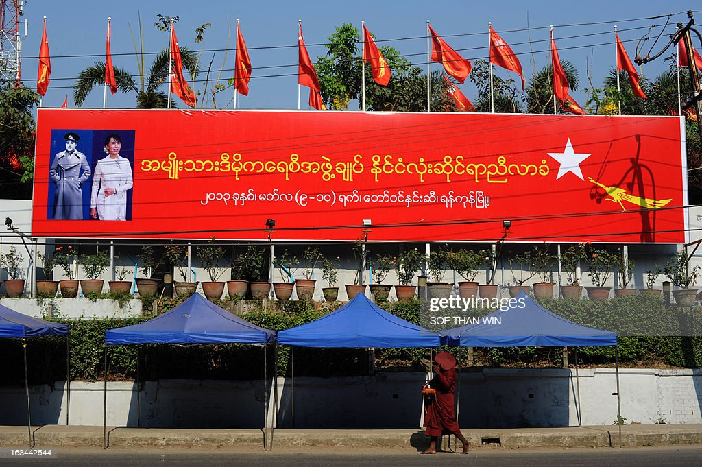 A Buddhist monk walks past a billboard announcing the congress of the National League for Democracy (NLD) outside the NLD's first ever party conference at the Royal Rose Hall in Yangon on March 10, 2013. Myanmar's long-silenced opposition on Sunday reappointed Nobel laureate Aung San Suu Kyi as party leader at a landmark maiden congress, as it eyes victory in elections due in 2015. AFP PHOTO/ Soe Than WIN