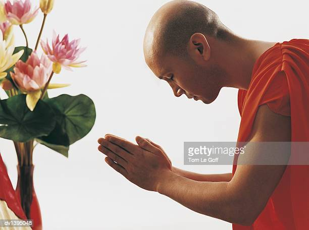 Buddhist Monk With Head Bowed in Prayer and Hands Together, Flowers in the Background