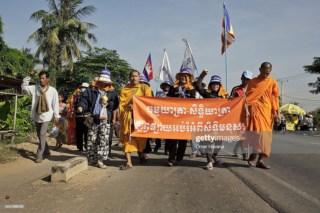 Buddhist monks and activist lead the 9th day of march on national road 1, 35 kilometers aways from Phnom Penh on December 8, 2013 in Phnom Penh, Cambodia. Over 500 Cambodian monks are marching in protest from December 1 - December 10 as they head to Phnom Penh to take part in coordinated anti-government protests, which will mark the 65th International Human Rights Day. Joining them are communities, associations, networks, federations, unions and NGOs, as well as residents of communities all along the six designated routes.
