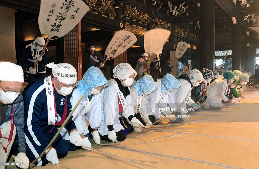 Buddhist monks and practitioners attend the annual dusting at Higashi Honganji Temple on December 20, 2013 in Kyoto, Japan. The dusting is in a traditional way, blowing the dust out of the hall with big fans while others raise the dust by hitting the tatami mat with bamboo branches.