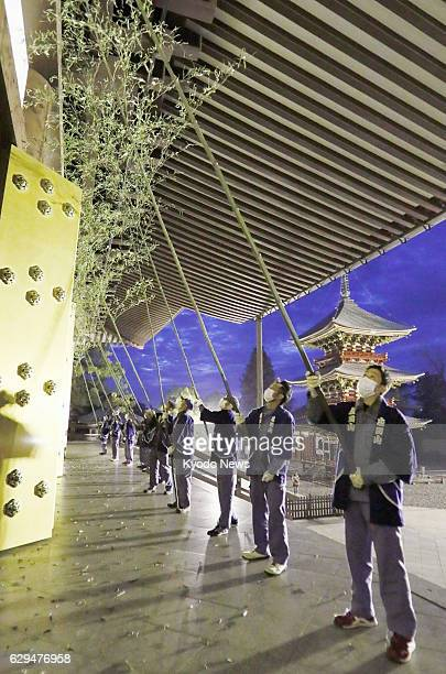 Buddhist monks and staff members of Shinshoji Temple in the central Japan city of Narita near Tokyo use 10meterlong bamboo tree trunks with leaves to...