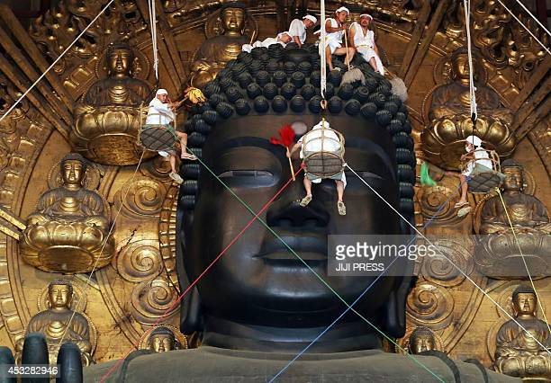 Buddhist monks and volunteers clean the 15metretall great Buddha statue during the annual Ominugui ceremony at Todaiji Temple in Japan's ancient...
