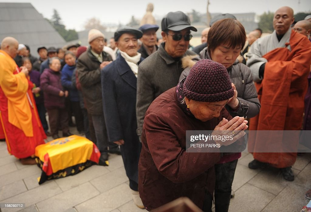 Buddhist monks (back L and R) bless Nanjing massacre survivors and their relatives as they pay their respects with others to victims on the 75th anniversary of the Nanjing massacre at the Memorial Museum in Nanjing on December 13, 2012. Air raid sirens sounded in the Chinese city of Nanjing on December 13 as it marked the 75th anniversary of the mass killing and rape committed there by Japanese soldiers -- with the Asian powers' ties at a deep low. AFP PHOTO/Peter PARKS