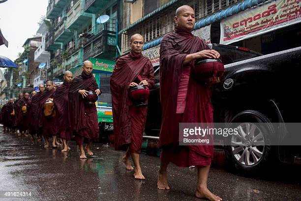 Buddhist monks carrying alms bowls walk barefoot along a street in Yangon Myanmar on Tuesday Oct 6 2015 Campaigning for Myanmar's Nov 8 general...