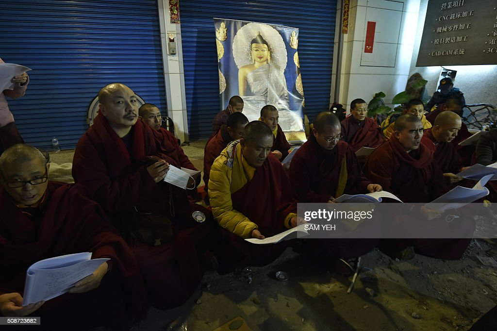 Buddhist monks chant prayers as rescue personnel continue work at the site of a collapsed building in the southern Taiwanese city of Tainan on February 6, 2016 following a strong 6.4-magnitude earthquake. A powerful earthquake in Taiwan felled a 16-storey apartment complex full of families who had gathered for Lunar New Year celebrations in the early hours of February 6, with at least seven dead and more than 30 feared trapped. AFP PHOTO / Sam Yeh / AFP / SAM YEH