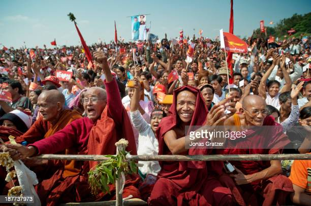 Buddhist monks cheer as Aung San Suu Kyi gives her speech in Mandalay during the NLD election campaign of 2012