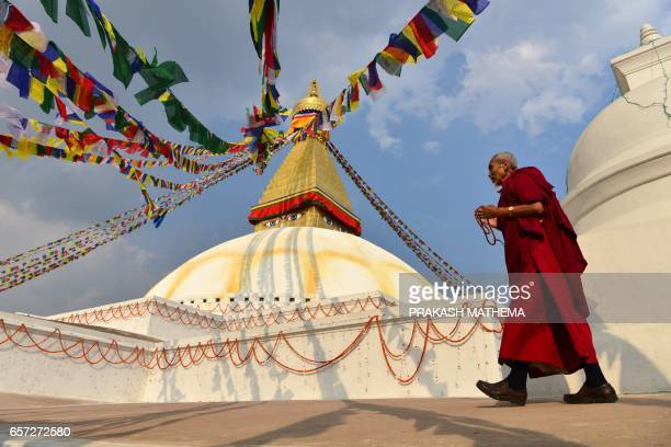 Buddhist monks circles Boudhanath Stupa on the outskirts of Kathmandu on March 24 2017 Boudhanath Stupa was among hundreds of historic monuments...