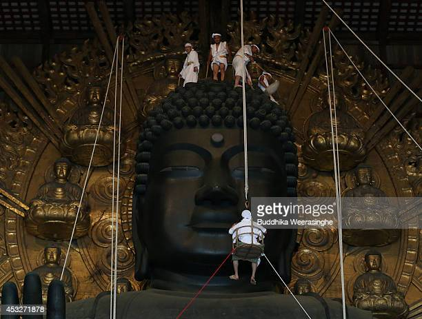 Buddhist monks clean dust off of the 15meterhigh Great Buddha at the Todaiji Temple on August 7 2014 in Nara Japan About 100 Buddhist monks take part...