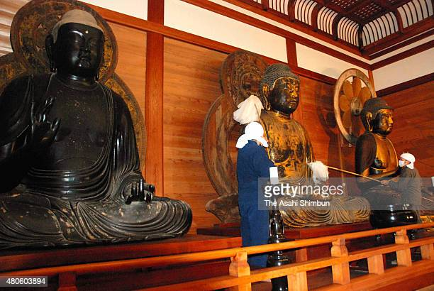 Buddhist monks clean the Budda statues as a part of the New Year preparation at Chusonji Temple on December 16 2011 in Hiraizumi Iwate Japan