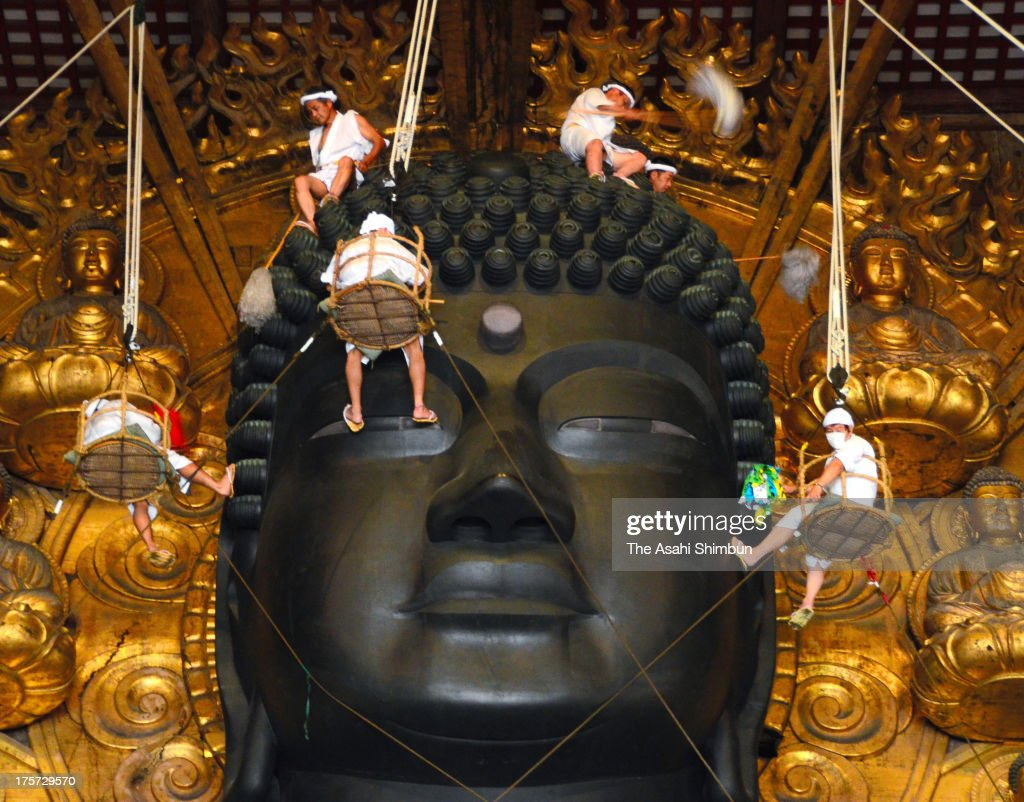 Buddhist monks clean the dust from the 15-meter-high Great Buddha at the Todaiji Temple on August 7, 2013 in Nara, Japan. The annual dusting is as a part of the preparation for the Buddhism festive period of 'Bon', around August 15, when Japanese buddhists honor and welcome the spirits of ancestors.