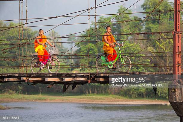 Buddhist monks cycling over Nam Song River bridge, Vang Vieng, Laos