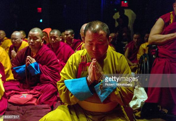 Buddhist monks pray as the Dalai Lama speaks at the Beacon Theater October 18 2013 in New York City The Dalai Lama is in New York for three days of...