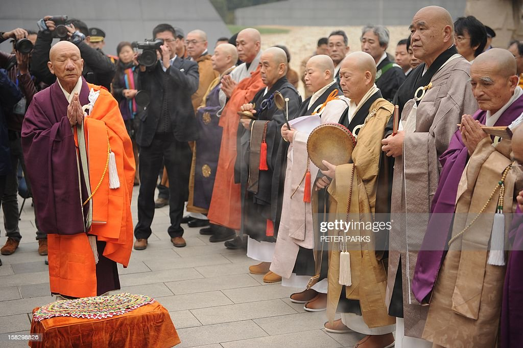 Buddhist monks pray for Nanjing massacre victims on the 75th anniversary of the Nanjing massacre at the Memorial Museum in Nanjing on December 13, 2012. Air raid sirens sounded in the Chinese city of Nanjing on December 13 as it marked the 75th anniversary of the mass killing and rape committed there by Japanese soldiers -- with the Asian powers' ties at a deep low. AFP PHOTO/Peter PARKS