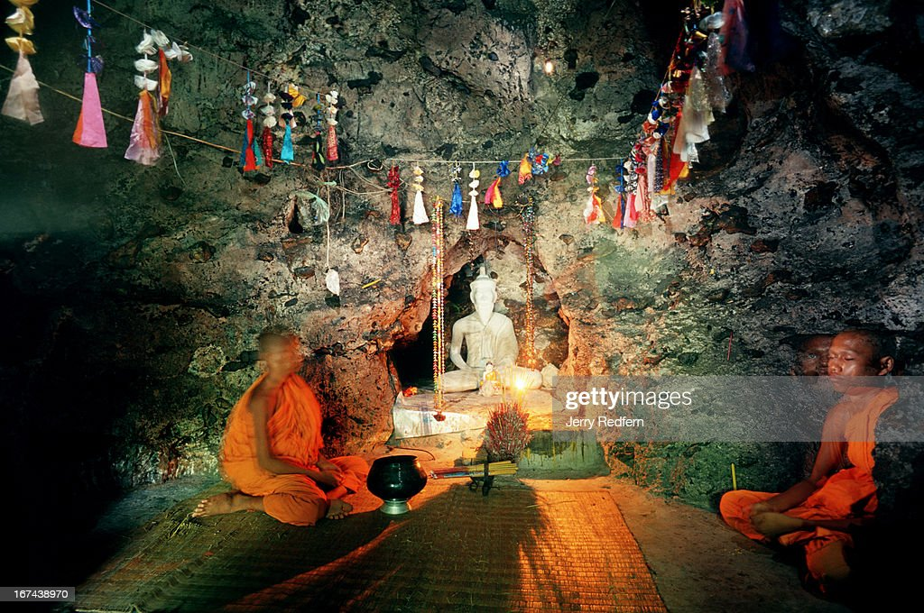 Buddhist monks pray in a cave atop Phnom Sampeau, a Buddhist holy spot about 20 km from Battambang. The Khmer Rouge used the hill as a killing ground, shoving people off of cliffs and into chasms on the hill and killing thousands..