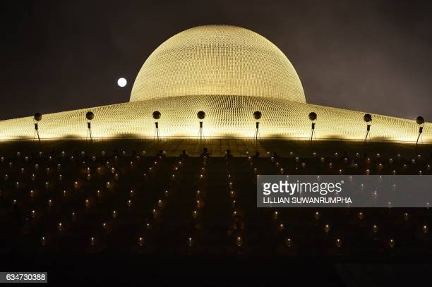 Buddhist monks pray with candles in front of a full moon to mark Makha Bucha Day at Wat Dhammakaya temple just north of Bangkok on February 11 2017...