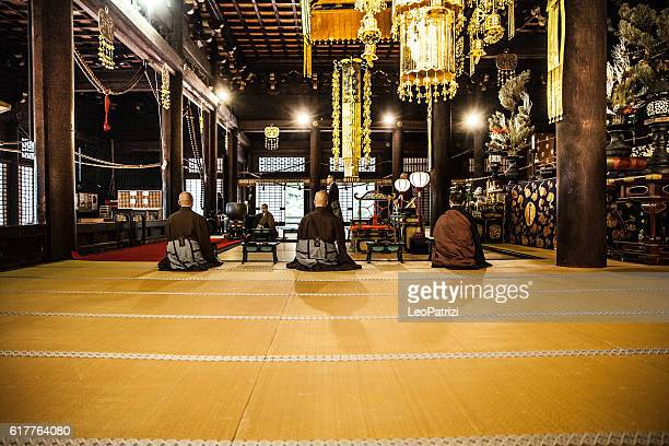Buddhist monks praying in early morning inside a Temple