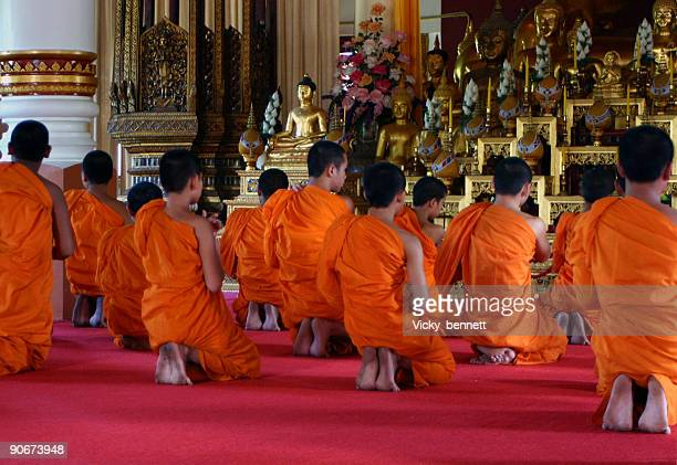 Buddhist monks praying in Thai temple.