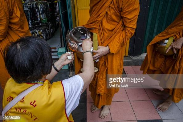Buddhist monks receive religious alms from a Buddhist follower as they walk around the streets during Pindapata procession on May 14 2014 in Magelang...