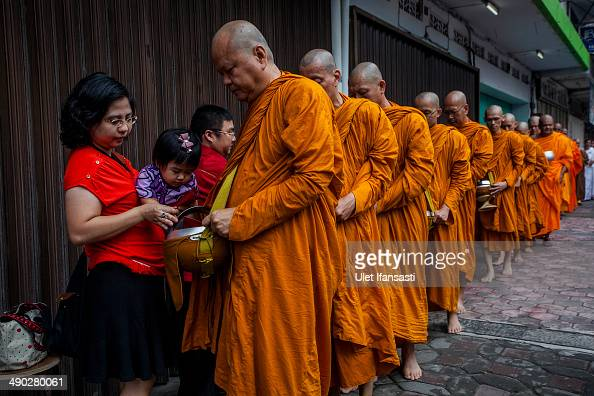 Buddhist monks receive religious alms from Buddhist followers as they walk around the streets during Pindapata procession on May 14 2014 in Magelang...