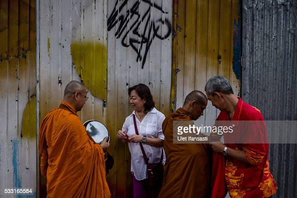 Buddhist monks receive religious alms from Buddhist followers as they walk around the streets during Pindapata procession on May 21 2016 in Magelang...