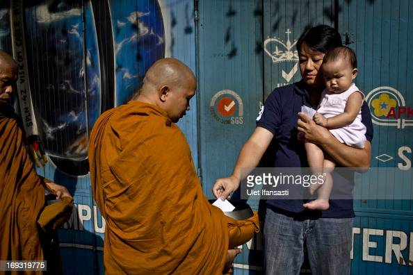 Buddhist monks receive religious alms from Buddhist members as they walk around the streets during Pindapata procession on May 23 2013 in Magelang...