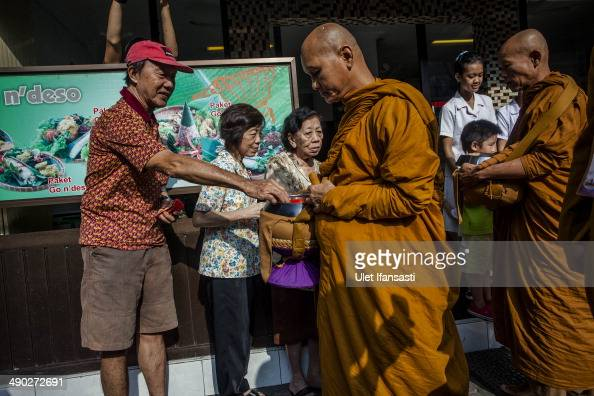 Buddhist monks receive religious alms from Buddhist members as they walk around the streets during Pindapata procession on May 14 2014 in Magelang...