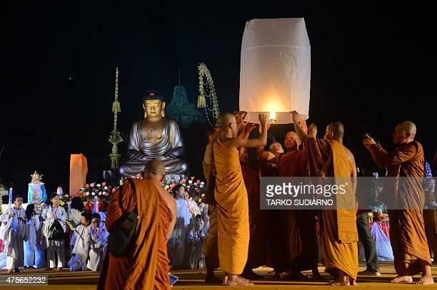 Buddhist monks release a fire lantern during a religious ceremony at the ancient Borobudur temple in Magelang late on June 2 in Indonesia's central...