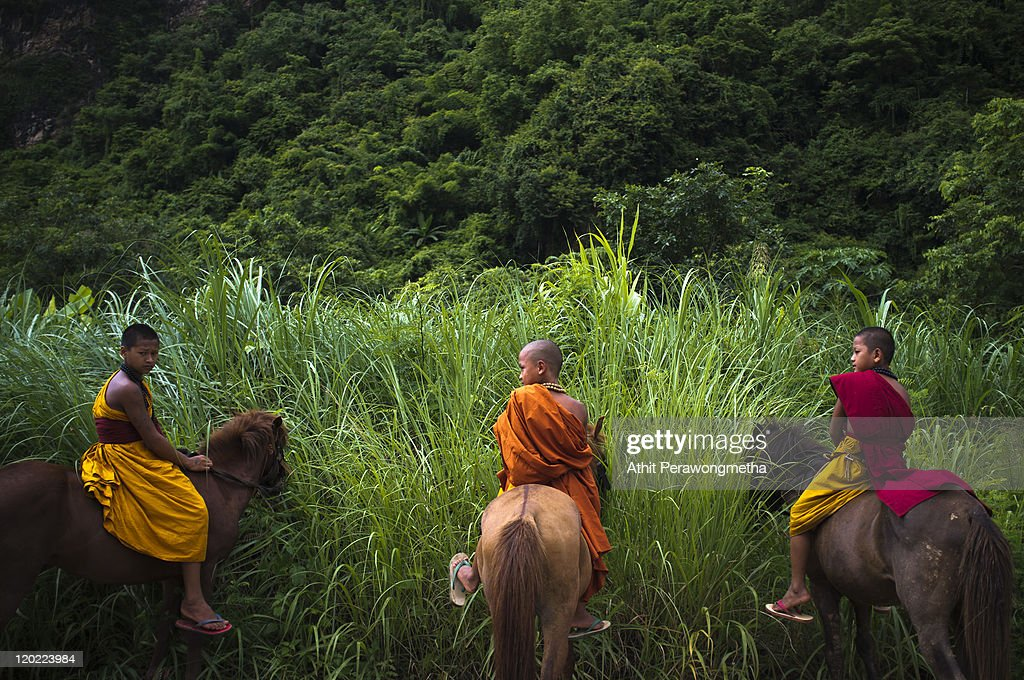 Buddhist monks sit on their horses during an afternoon duty on August 1, 2011 in Chiang Rai, Thailand. The monastery, founded by former Thai boxing champion Phra Kru Ba Neua Chai who became a Buddhist monk , takes in destitute children, training them in equestrian skills on horses, many of which have been saved from slaughterhouses, and Thai boxing. .