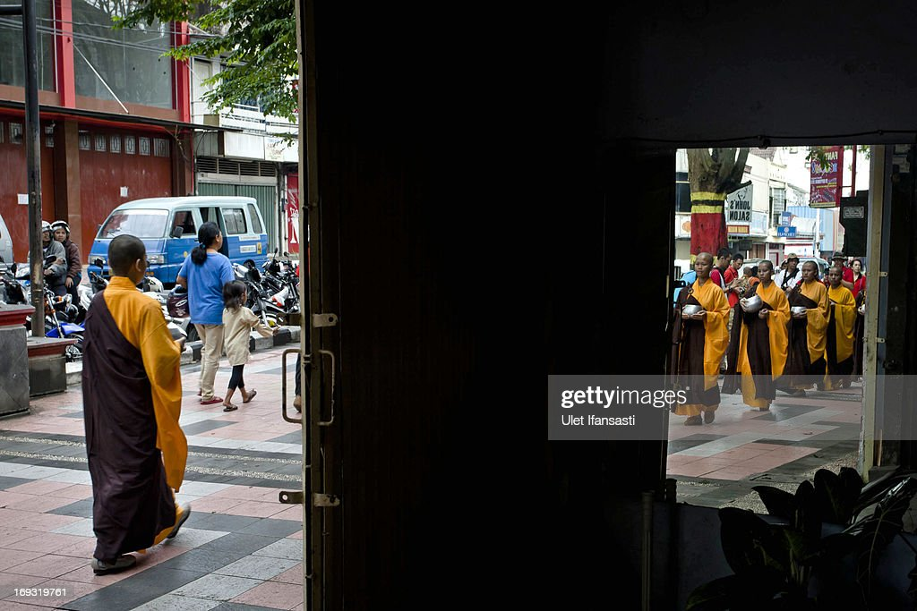 Buddhist monks walk around the streets to receive religious alms from Buddhist members during Pindapata procession on May 23, 2013 in Magelang, Central Java, Indonesia. As many as 100 monks took to the streets of Magelang city in a procession known as Pindapata, ahead of Vesak day which celebrates the birth of the Lord Buddha.