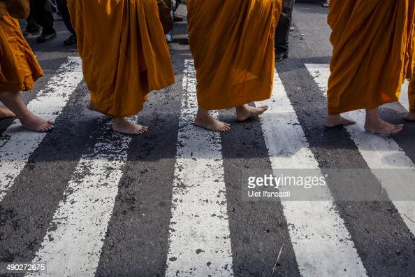 Buddhist monks walk around the streets to receive religious alms from Buddhist followers as they walk around the streets during Pindapata procession...