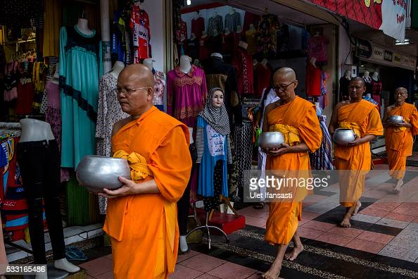 Buddhist monks walk around the streets to receive religious alms from Buddhist followers during Pindapata procession on May 21 2016 in Magelang...