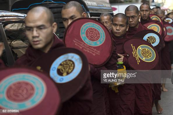 TOPSHOT Buddhist monks walk in procession to collect alms in downtown Yangon on January 17 2017 / AFP / Ye Aung THU