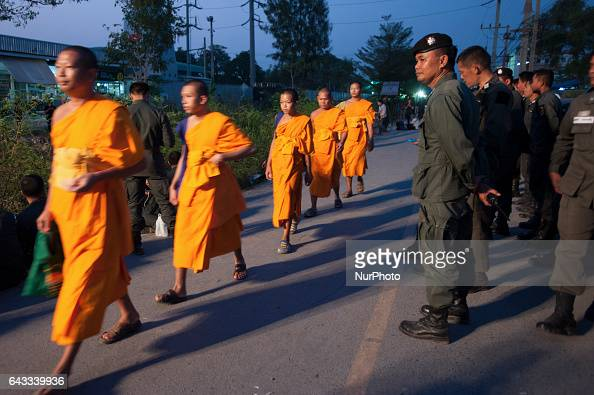 Buddhist monks walk past a policeman at the gate of Dhammakaya temple in Pathum Thani province on the outskirts of Bangkok Thailand on February 20...