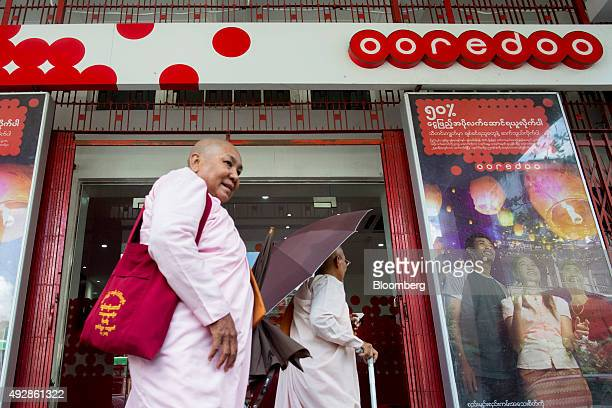 Buddhist monks walk past an Ooredoo QSC store in Yangon Myanmar on Thursday Oct 15 2015 Ooredoo is pushing mobileInternet plans to subscribers from...