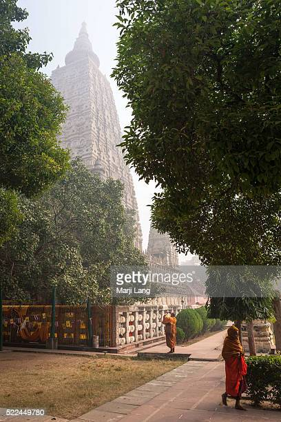 BODHGAYA BIHAR INDIA BODHGAYA BIHAR INDIA Buddhist monks walking by a misty morning in the gardens around the Mahabodhi Mahavihara temple in Bodhgaya...
