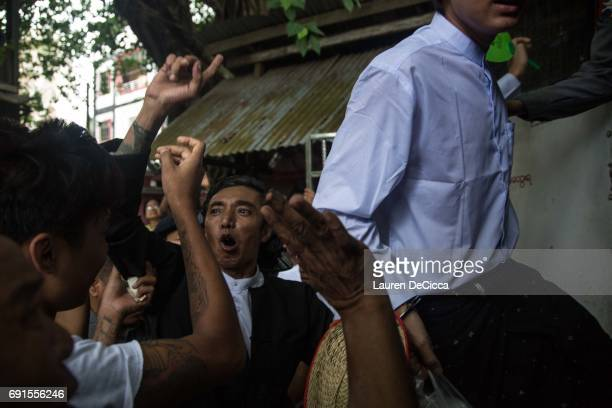 Buddhist Nationalist Leader Ko Latt shouts to his followers before being put back into police van as he exits his trial on June 2 2017 in Yangon...
